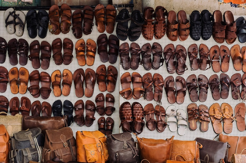 picture of different styles and colors of sandals and  purses on a wall