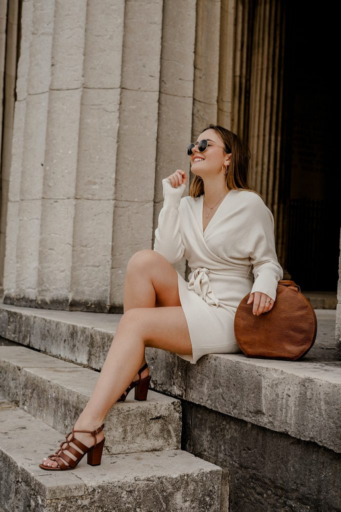 picture of a girl sitting on old stairs outdoors wearing white casual dress, glasses, brown purse and brown casual sandals
