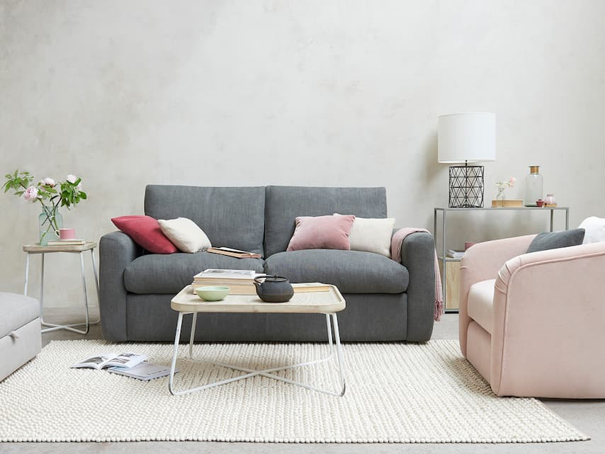 modern grey sofa bed with decorative pillows coffee table and side tables