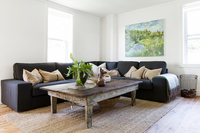 dark grey sofa bed with wood table and decorative vessel